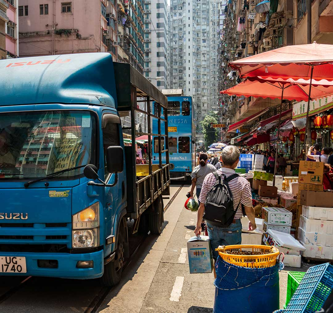 Hong Kong - Truck and tram going through a Street Market in North Point