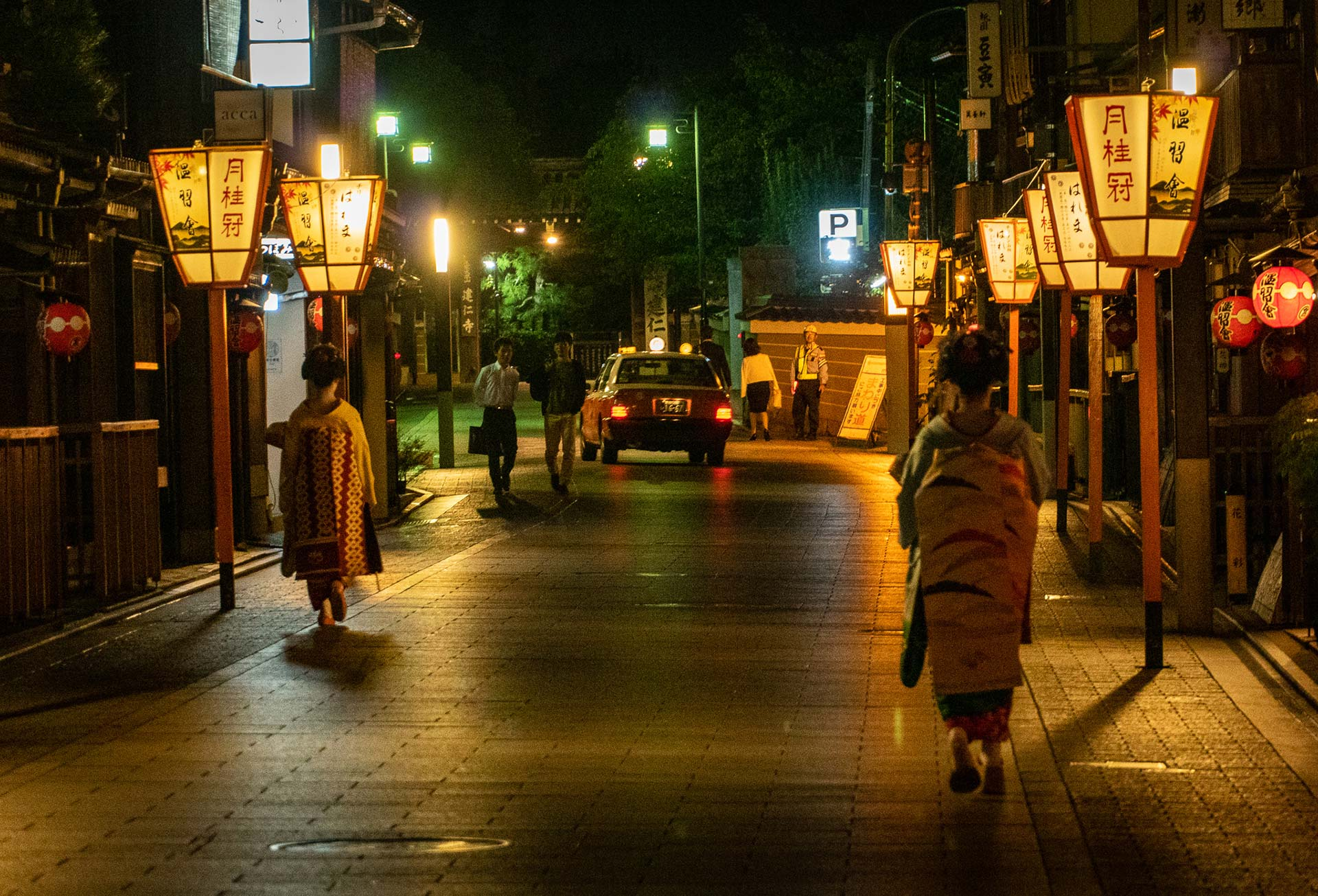 2 geishas walking the streets of Gion between gigs