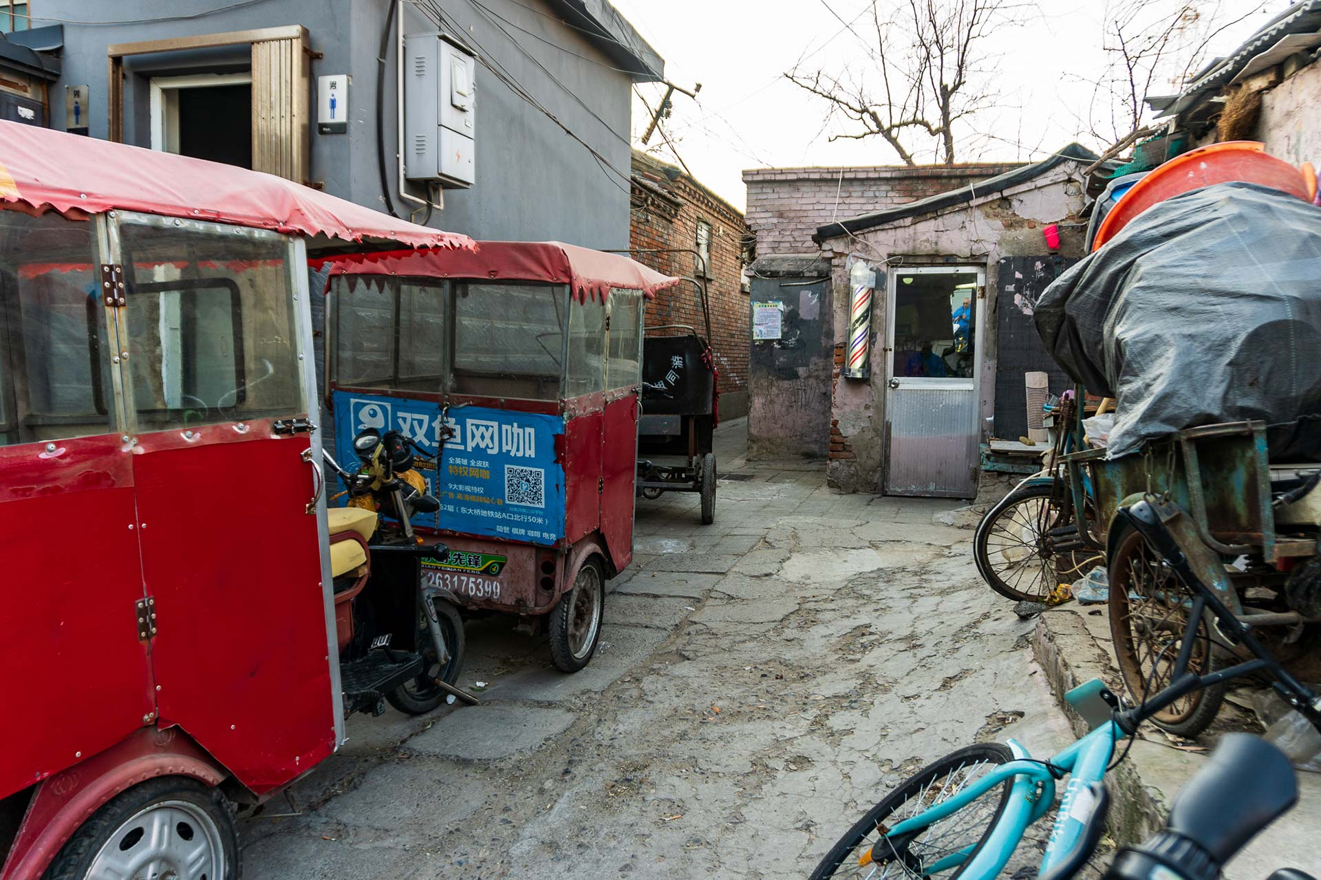 Hutong Barbershop surrounded by tuk tuks, bikes and junk
