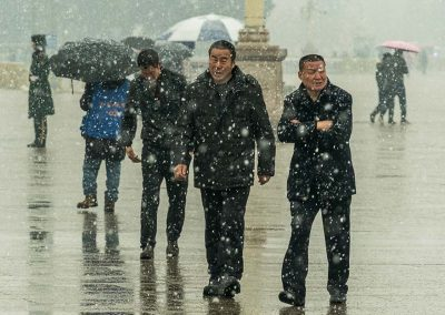 Tourists walking Tiananmen Square in the snow